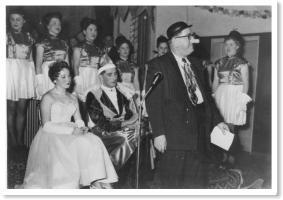 Konrad Bemsel als Büttenredner beim Faschingsball der Musikvereinigung 1955 in der Festhalle Ay. Im Hintergrund das Prinzenpaar und die Prinzengarde der Musikvereinigung.